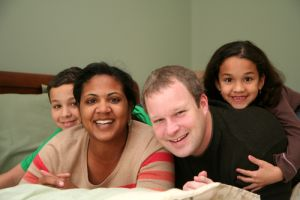 Inter-Racial Family Relaxing On A Large Bed